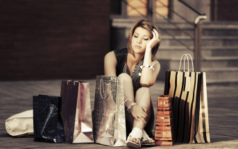 woman with shopping bags feeling buyer's remorse