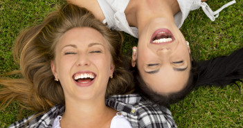 happy women lying on grass