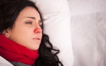 girl lying on bed with red nose and flu