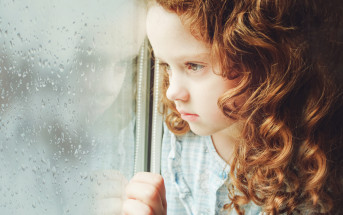sad girl looking out of window at rain