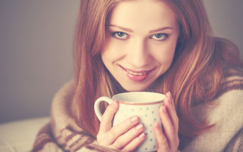 young woman drinking hot drink with blanket