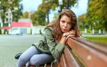 introverted woman sitting on bench