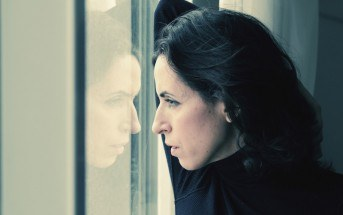 woman looking regretfully out of window