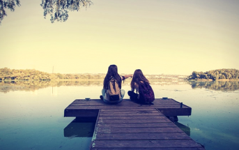 two girls sitting on pier