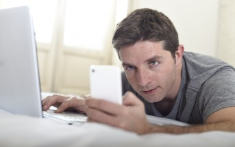 man checking phone and laptop