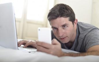 man checking phone and laptop