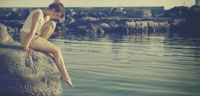 sad woman looking into ocean