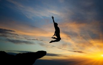 silhouette of man leaping from rock