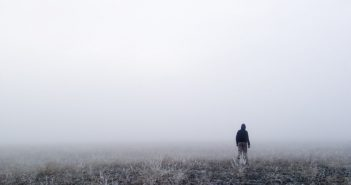 person walking alone in mist and fog