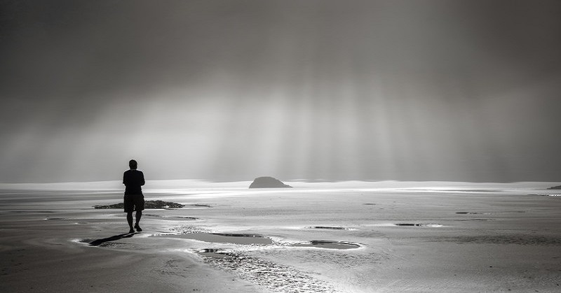 man walking on misty beach