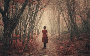 woman walking in misty woods