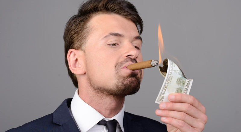 arrogant man burning money with cigar