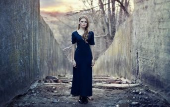 woman in dark dress between grey walls