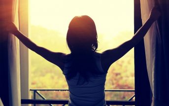 woman opening curtains on sunny day