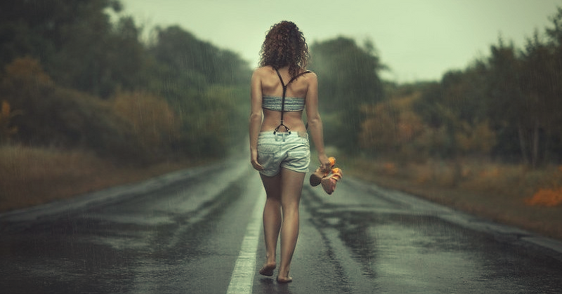 woman walking barefoot along road