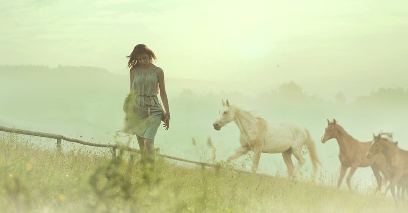 introvert woman with horses in the background