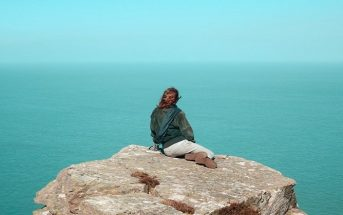 universal truths - woman sitting on clifftop