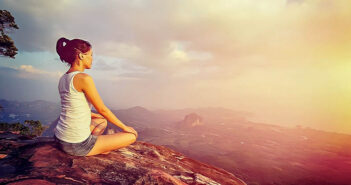 woman meditating on mountain - concept of inner peace