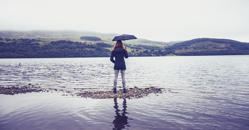 woman with umbrella at lake - concept being humble