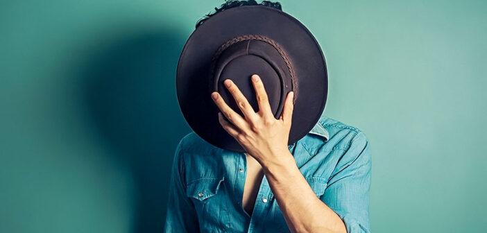man covering face with hat - concept of covert narcissist
