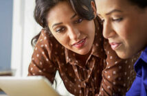 two women looking at tablet - concept of interpersonal skills