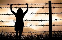 woman trapped by barbed wire fence - concept of victim mentality