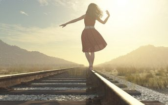 woman walking on railway track in sun