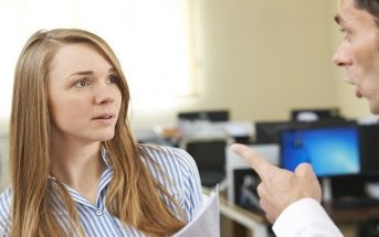 male boss pointing finger at female coworker - concept of control freak
