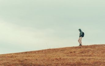 man walking down barren hill - concept of existential trap