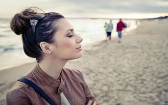 woman eyes closed on beach - concept of highly sensitive person