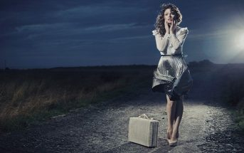 woman with suitcase on dark path - fear of change