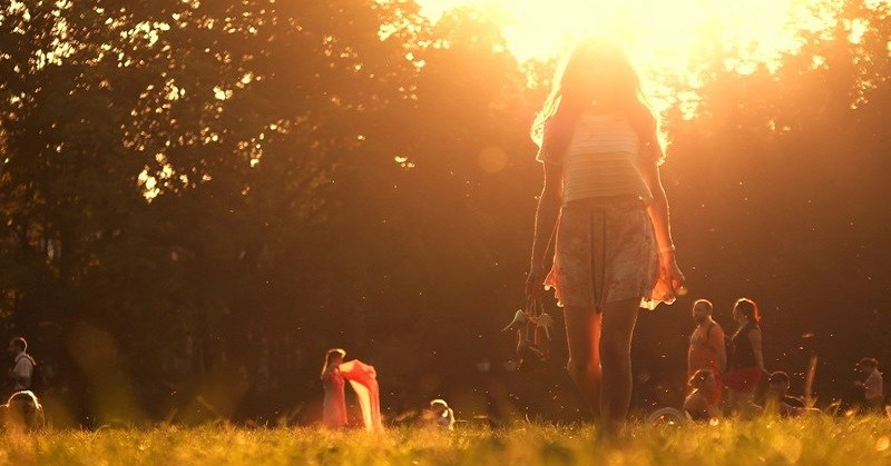 woman walking barefoot with sun in background - concept of free spirit
