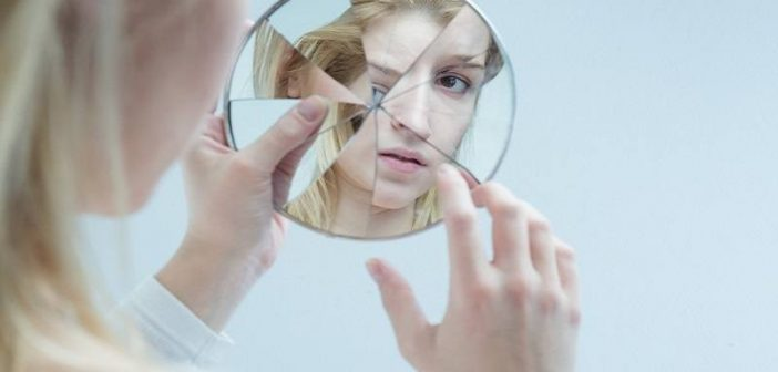woman looking in cracked mirror - concept of self-loathing