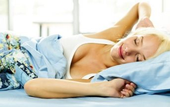 woman stretching waking up in bed