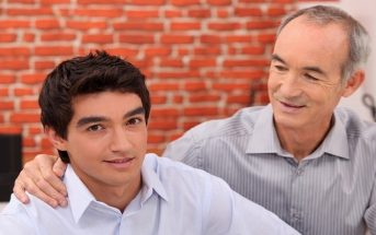man with encouraging hand on grandson's shoulder