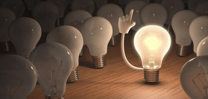 illustration of lightbulb with hand surrounded by other lightbulbs - concept of leadership