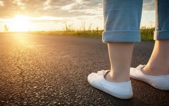 woman's feet on path towards sun