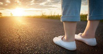 woman's feet on path towards sun