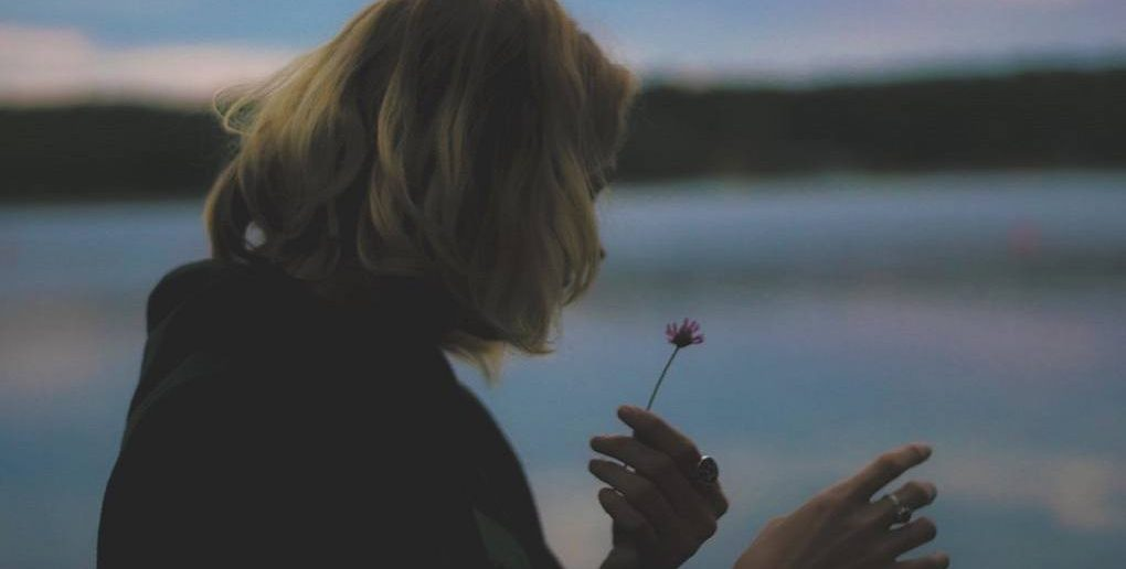 young woman pulling petals from flower as a hopeless romantic would