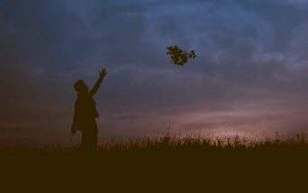 silhouette of person throwing flowers into the sky, thus letting go of the past