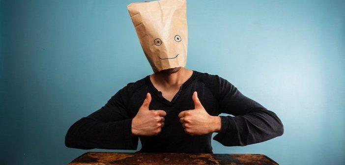 man with two thumbs up and a paper bag over his head signifying a people pleaser