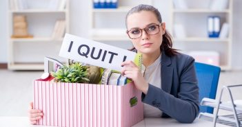 "woman with box of possessions and ""I quit"" sign"