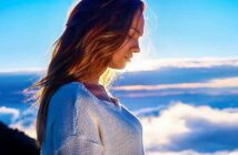 young woman looking down with clouds in background - concept of spiritual maturity