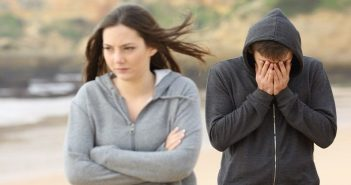 young woman walking away from man after breaking up with him