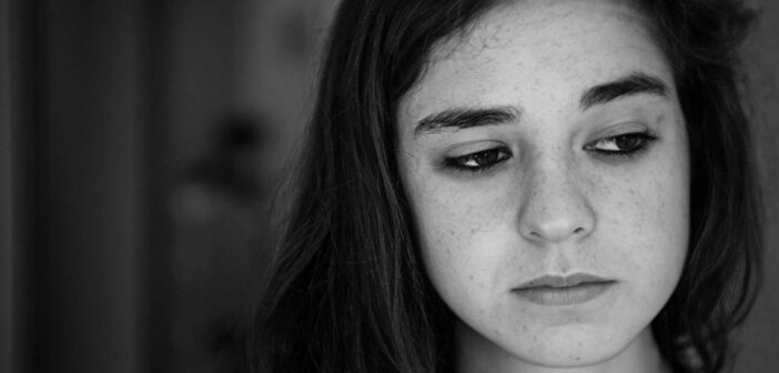 black and white photo of sad looking young woman feeling worthless