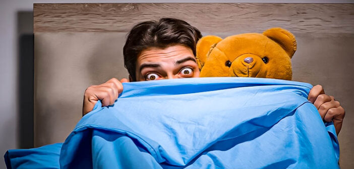 man with teddy bear hiding behind duvet - demonstrating immaturity