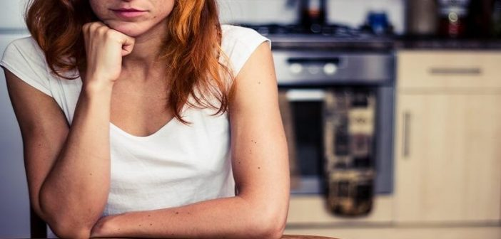 bored looking woman sitting at kitchen table - indicating a lack of motivation