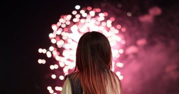 woman looking at fireworks to signify New Year's resolutions