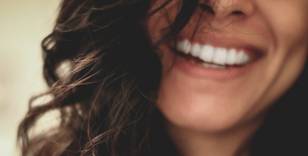 closeup of smiling woman to denote a positive person