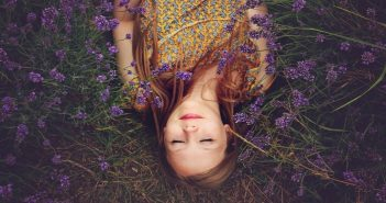 young woman lying in a field of lavender showing a spirit that needs to wake up